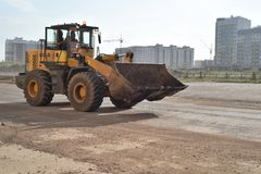 Russian SDLG Earthmover on Road. Modern SDLG LG953 earthmover machine in dirt stained yellow travels along an empty Road Royalty Free Stock Image
