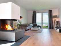 Modern seaside living room. Modern living room with fireplace and a view to the sea Stock Images