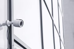 Modern security CCTV camera. On wall outdoors stock image