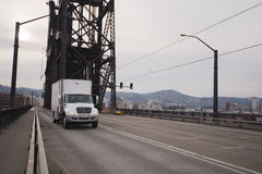 Modern semi truck midle class power on old bridge in down town P Stock Photos