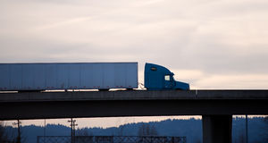 Modern semi truck trailer on overpass bridge evening silhouette Royalty Free Stock Photography