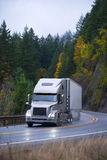 Modern semi truck trailer in rain autumn winding road Stock Photo