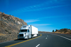 Modern semi truck and trailer on turning rocky windy road. Modern long haul commercial cargo pro power silver big rig semi truck with trailer and aerodynamic to stock image