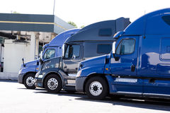 Modern semi trucks profiles on truck stop. Modern popular models of heavy trucks are shades of blue in a row on a truck stop for drivers' rest and refueling of Stock Photography