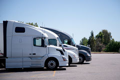 Modern semi trucks stand in row on truck stop parking space Royalty Free Stock Photo
