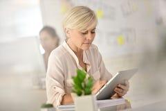Modern senior businesswoman with tablet Stock Photos