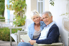 Modern senior couple connected to wifi Stock Images