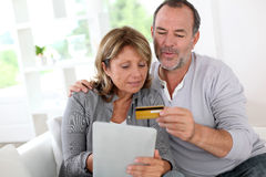 Modern senior couple at home shopping with tablet Royalty Free Stock Photography