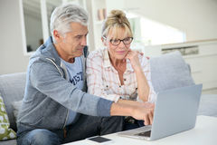 Modern senior couple at home using laptop Royalty Free Stock Photos