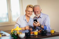 Senior couple shopping online with phone and credit card royalty free stock photography