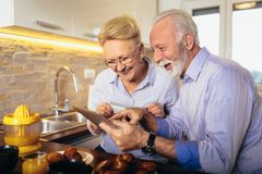 Senior couple shopping online with tablet and credit card. Modern senior couple shopping online with tablet and credit card royalty free stock photo