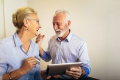 Senior couple shopping online with tablet and credit card stock photo
