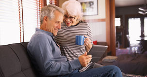Modern senior couple sitting on couch with tablet.  Royalty Free Stock Image