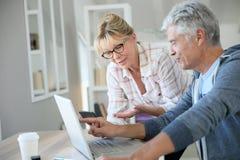 Modern senior couple using laptop Stock Image