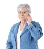 Modern senior lady on mobile phone. Elderly lady standing over white background, talking on mobile phone, smiling Royalty Free Stock Photos