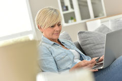 Modern senior lady using laptop at home Stock Images