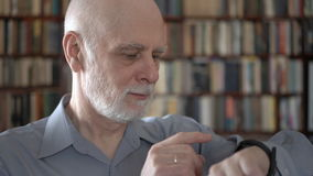 Modern senior man at home using smartwatch, browsing, reading. Bookcase bookshelves in background stock video footage