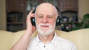 Modern senior man listening music with wireless headphones. Pensioner meloman dancing to music
