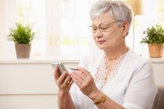 Modern senior woman with pda. Portrait of modern senior woman using pda at home, smiling Royalty Free Stock Image