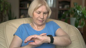 Modern senior woman sitting on yellow chair at home using her black smartwatch, browsing, reading stock video footage