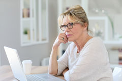 Modern senior woman thinking and using laptop Royalty Free Stock Photos