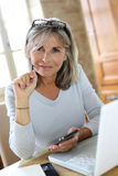 Modern senior woman using laptop and smartphone Royalty Free Stock Photo