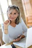 Modern senior woman using laptop and smartphone Royalty Free Stock Photo
