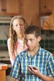Modern ser questioningly som hennes tonåriga sonkontroller hans telefon Arkivfoto