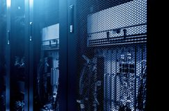 Modern server rack cluster under meshed door in big data centre with blue neon toning. Close up. Internet provider. Control. Network and technology futuristic royalty free stock image