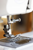 Modern Sewing Machine. Close-up of modern sewing machine, with focus on needle.  Blurred background Royalty Free Stock Photos