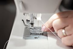 Modern sewing machine close-up threading needle - image stock photo