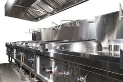 Modern shiny and clean kitchen with stainless steel kitchenware, stove, exhaust, and equipment for restaurant-scale cooking. Isolated on restaurant kitchen stock photo