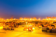 Modern shipping harbor at night. Shanghai container terminal at night with bright lights, busy modern harbor background Stock Photo
