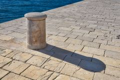 A stone bollard by the sea. An modern ships bollard, shaped from marble, set into limstone quayside with azure Adriatic sea as a background. Casts a long shadow Royalty Free Stock Photography