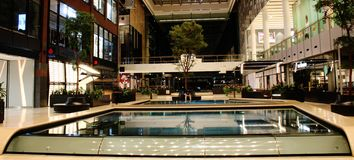 Modern shopping mall with trees and water inside royalty free stock photo