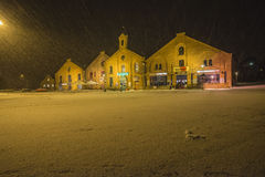Modern shops in old brick buildings (at night and in the blizzar. The buildings are located at the Tista river in Halden, Norway and houses a grocery store Royalty Free Stock Image