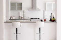 Modern Showcase Kitchen Interior in White. Home interiors: a clean and bright modern kitchen royalty free stock image