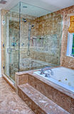 Modern Shower and Bathtub in Room. This modern bathroom features a clear glass shower with marble enclosure, and a pretty white bathtub. All surrounded with stock photography