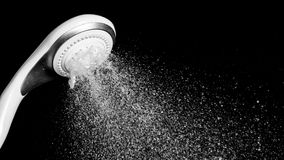 Modern shower head with running water isolated on black backgrou Royalty Free Stock Image