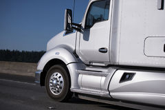 Modern silver big rig semi truck driving by interstate highway. Modern smooth bonnet classic pearl silver big rig semi truck with aerodynamic body for fuel Stock Photos