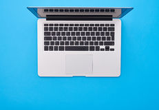 Modern silver laptop lying on the blue flatlay with a place for Royalty Free Stock Images