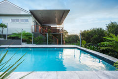 Modern simbassäng med blått vatten bredvid ett hus arkivbild