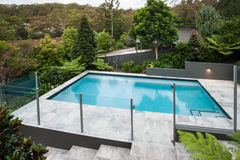 Modern simbassäng med ett glass staket på golvet royaltyfria bilder