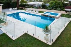 Modern simbassäng som täckas med glass paneler bredvid en gräsmatta arkivfoto