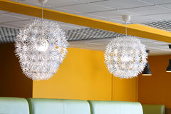 Modern simple lamps with white shades in empty cafe Stock Image