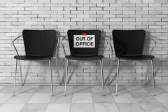 Modern Simpne Office Chairs One with Out of Office Sign. 3d Rend. Modern Simpne Office Chairs One with Out of Office Sign in front of Brick Wall. 3d Rendering Royalty Free Stock Image