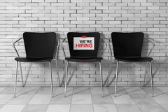 Modern Simpne Office Chairs One with We're Hiring Sign. 3d Ren. Modern Simpne Office Chairs One with We're Hiring Sign in front of Brick Wall. 3d Royalty Free Stock Photography