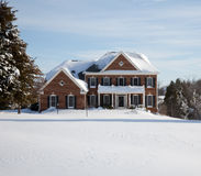 Modern single family home in snow. Modern home in a snowy setting with a conifer in the foreground stock photo