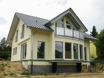 Modern single-family house with glass front. View onto the glass front of a newly constructed yellow single-family house Stock Photography