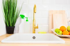 Modern sink and faucet in the kitchen room. Kitchen interior. Golden metal faucet and modern sink, next to which are cleaning products, houseplant, fruit and royalty free stock images